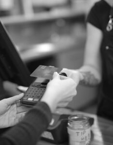 Displays a person checking out at a register and completing a payment using a POS system