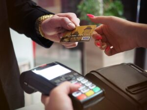 Person handing a credit card to a merchant to make a payment for services and or products purchased.